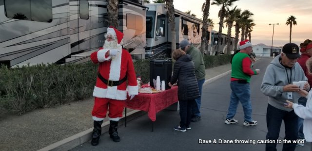 Santa directing people to the hot coco and cookies.